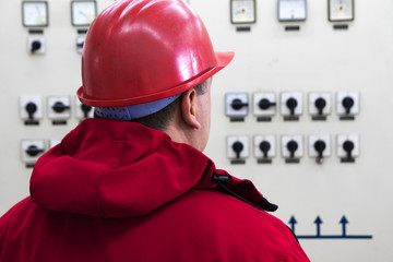 Engineer with red  helmet reading instruments in power plant control center