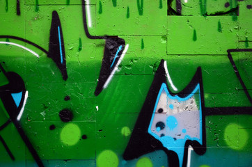 A fragment of graffiti drawing using contours, applied to the wall with the help of cans with aerosol paints over the colored filling areas. Background texture of street art and vandalism