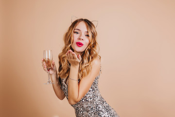 Lovely blonde girl in sparkle attire sending air kiss standing on light background with wineglass. Indoor photo of gorgeous caucasian woman with curly hair relaxing at party.
