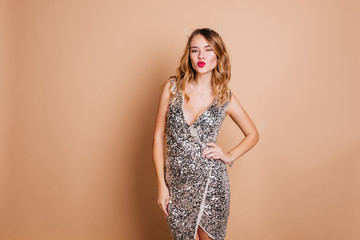 Elegant caucasian woman with curly hairstyle posing with kissing face expression at chrismas party. Charming birthday girl in sparkle dress standing in confident pose on light background.