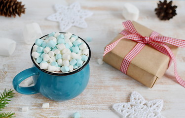 Cup of Chocolate with Marshmallows, Christmas Decorations on Wooden table, Pine Branch, Snow Down, Toned Photo