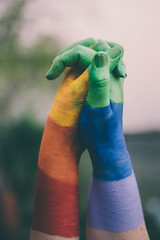 Hands painted in Gay pride rainbow.