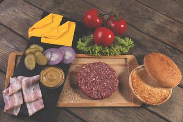 Fototapete - homemade cheeseburger fresh ingredients cheese, bun, salted cucumber, beef patties,bacon