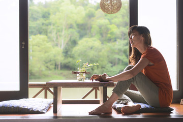 Young woman sits near window with green forest and lake