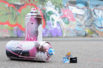 Several used spray cans with pink and white paint and caps for spraying paint under pressure is lies on the asphalt near the painted wall in colored graffiti drawings
