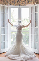 Bride in classic wedding dress looking over balcony through french doors