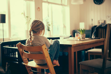 Young girl sitting lonely at the kitchen table