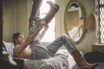 Shirtless Man in Jeans Struggling to Put Boots on in Bed