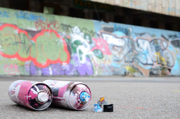 Several used spray cans with pink and white paint and caps for spraying paint under pressure is...