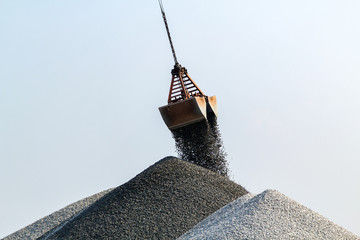 Crane moving amd unloading gravel stones on a mountain.
