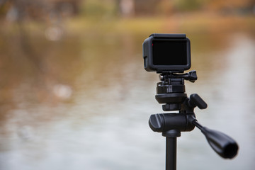 action camera on tripod beside lake.