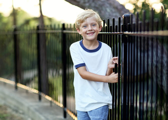 smiling boy beside a fence