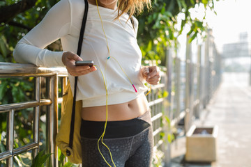 Young female runner is having break and listening to music during the run in city