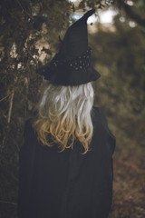Girl wearing witch costume at Halloween in the forest