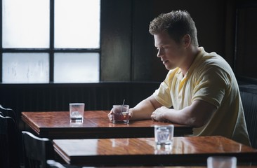 Young man sitting at bar table with drink