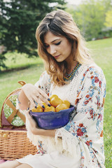 Woman with a bowl of oranges picnicking outdoors