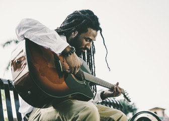 Young Man with Dreadlocks Playing Guitar