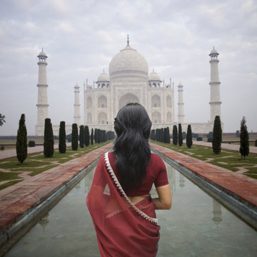 Indian woman standing in front of Taj Mahal. India.