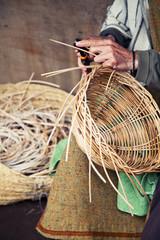Older hands making a wicker basket