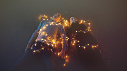 Couple lying down covered in lights