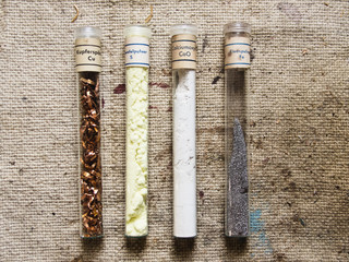 four old test tubes with different chemicals for testing on an old cloth