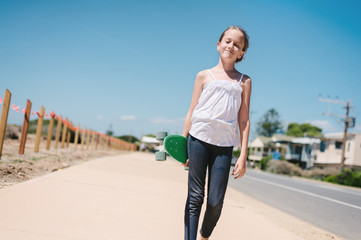 girl walking along the sidewalk carrying a skateboard, smiling
