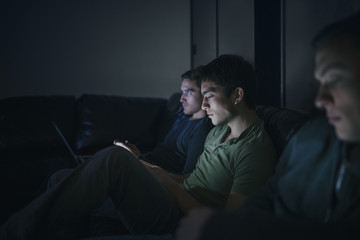 Student Friends and Rommates Watching TV together and Using Smartphones and Laptop