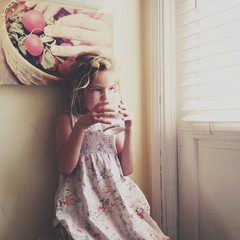 young girl drinking by window in kitchen