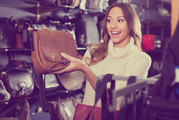 Young attractive woman buying leather purse in shop