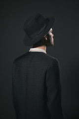 Dark portrait of the back of the man, wearing a hat against a black backgorund