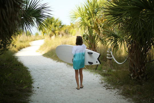 Girl Carrying Her Surfboard to the Beach