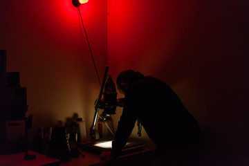 Man working in darkroom.
