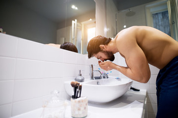 Strong muscular shirtless man washing face in the bathroom.