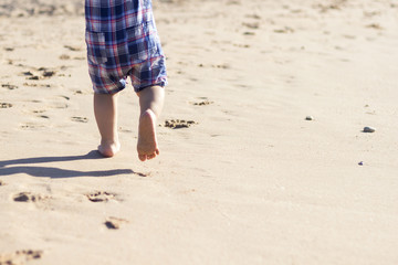 Legs of children stand on the beach. Baby feet in the sand. Summer beach background. Summertime holidays concept. Copy space