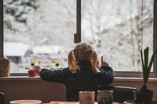 Little girl gazes out window at the snow.