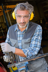 Portrait of man using angle grinder
