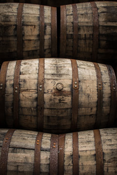 Wooden barrels and casks sit in a pile