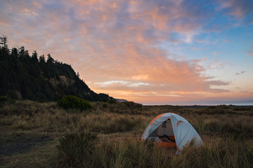 Sunset on the Northern California coast with a tent pitched in the beach grass.