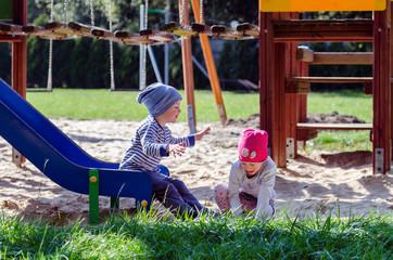 Fototapeta Rodzeństwo dzieci bawi się na planu zabaw w jesienny słoneczny dzień. obraz