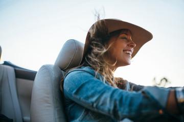 Pretty woman having fun driving convertable car on sunny summer day