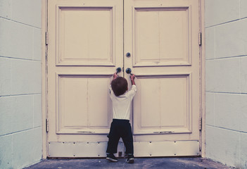 Toddler Boy Trying to Open Double Doors