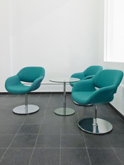Three blue-green colored chairs in a waiting area