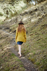 Redhead woman walking on narrow trail