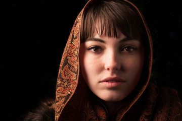 Young woman wearing a headscarf shot in a Chiaroscuro like style