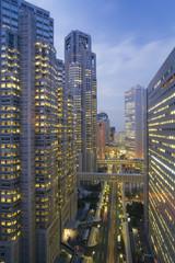 Asia, Japan, Honshu, Tokyo, Shinjuku, Shinjuku office buildings and street illuminated at dusk - elevated view