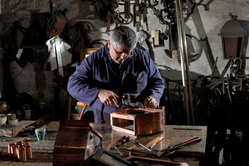 An Italian blacksmith in his workroom creating a lantern