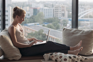 woman with laptop by the window