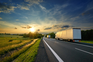 Fotobehang - Trucks driving towards the setting sun on the road in rural countryside