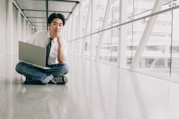 Casual Young Asian Business Man Sitting in a White Space with a Laptop
