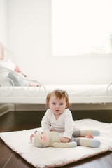 cute Baby sitting with lamb doll on floor